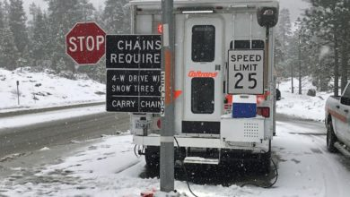 "Highway department truck with ""Chains Required"" sign along a snowy California road."