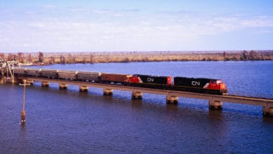 A photograph of a freight train crossing a long bridge.