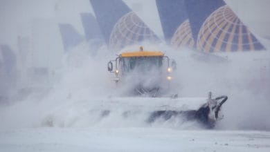 Plow trucks clearing runways at Denver International Airport.