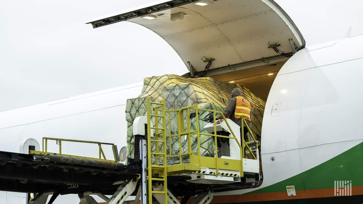 Cargo pallets on a hydraulic lift being unloaded out of side door of large aircraft with white fuselage.