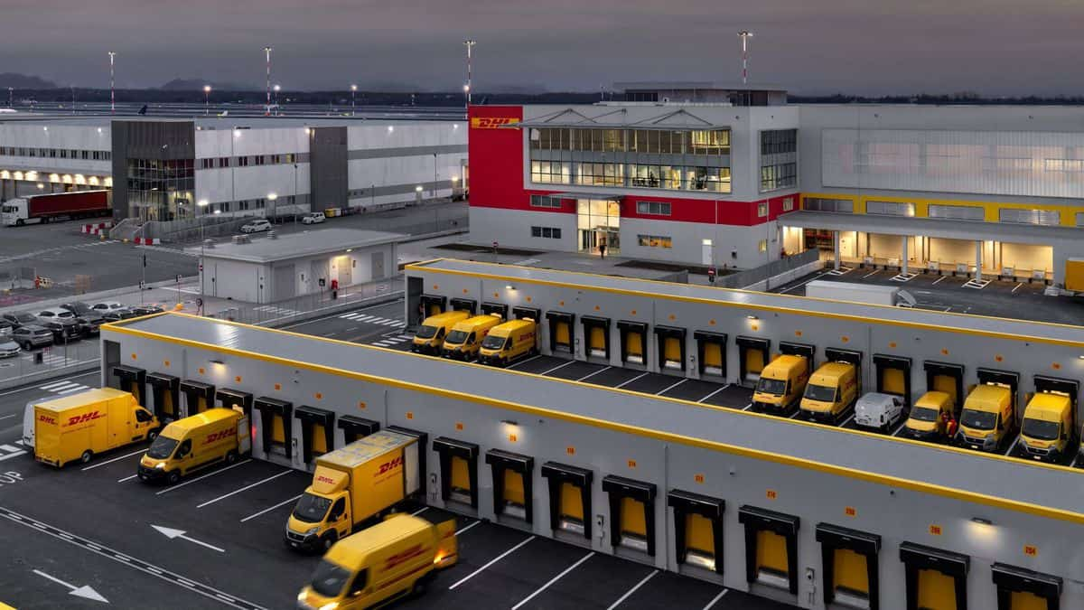 Yellow delivery vans at DHL warehouse loading doors.