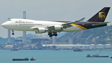 A white UPS jumbo jet with brown tail coming in for landing over water by Hong Kong Airport.