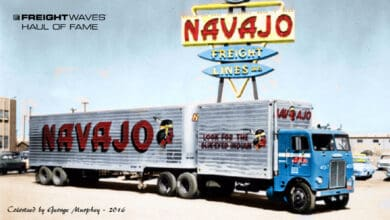 A Navajo tractor and two trailers parked under the Navajo sign. (Photo colorized by George Murphey)
