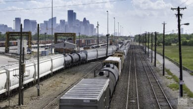 A photograph of a rail yard. A city is in the distance.