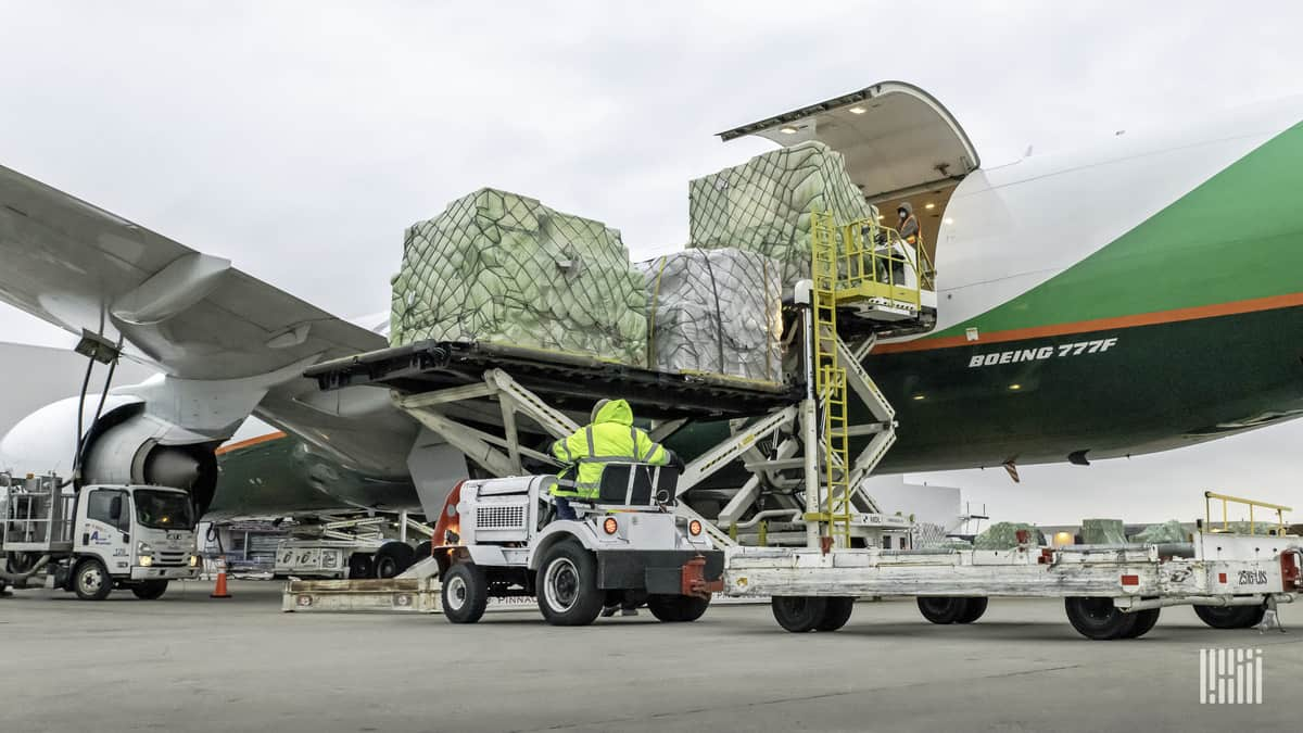 A white and green plane loading pallets of cargo through side door.