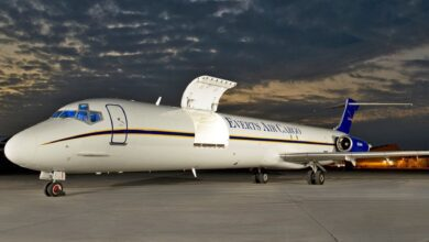 A white MD-88 aircraft with side cargo door open at night.
