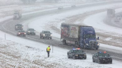 Tractor-trailer and cars heading down Nebraska highway on a snowy day.