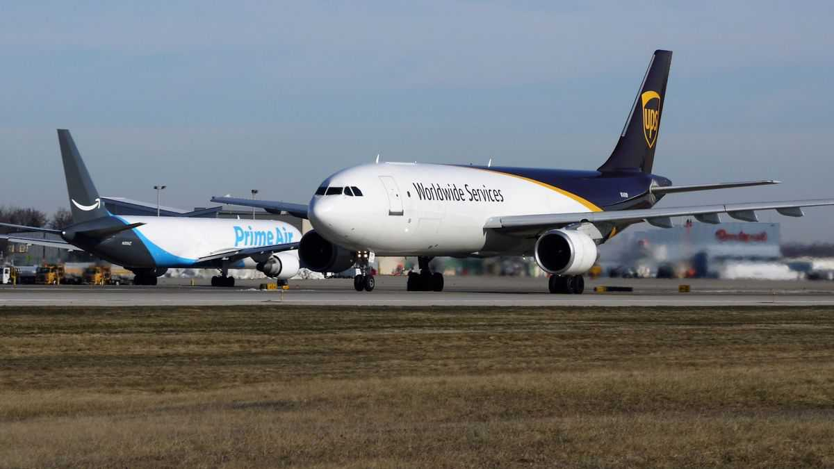 White jets with brown and blue tails at airport passing in opposite directions. Amazon and UPS planes.