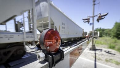 A photograph of a train passing by a rail crossing.
