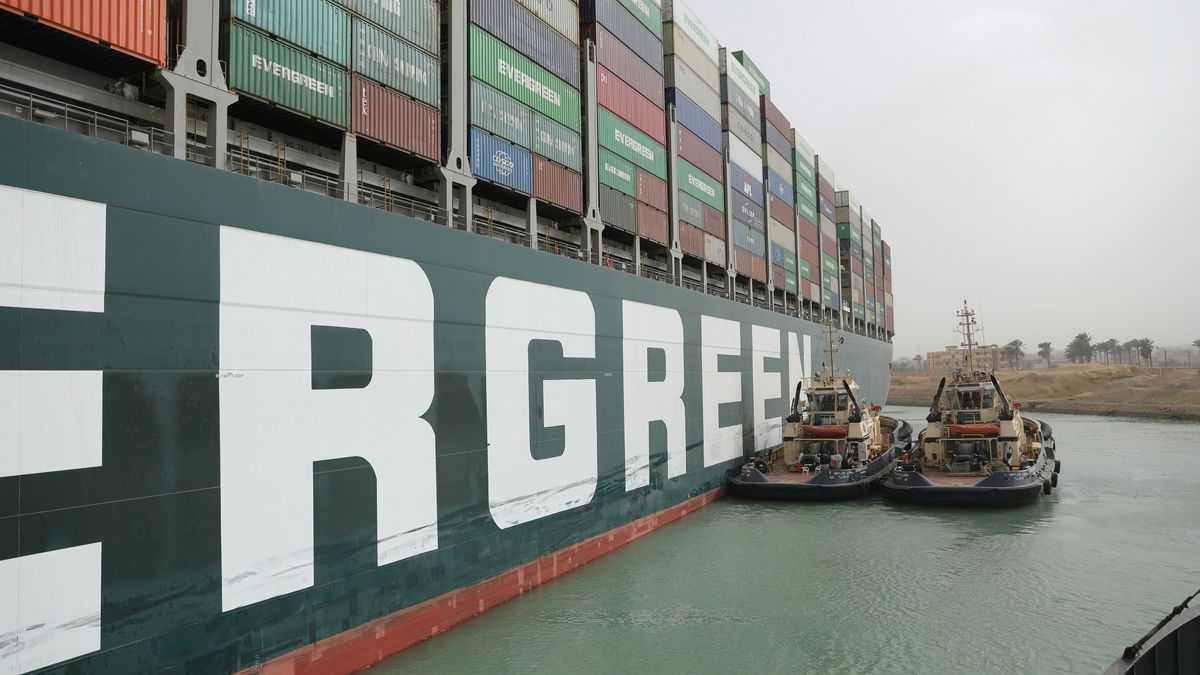 Tug boats try to move a big green container ship stuck in the mud.