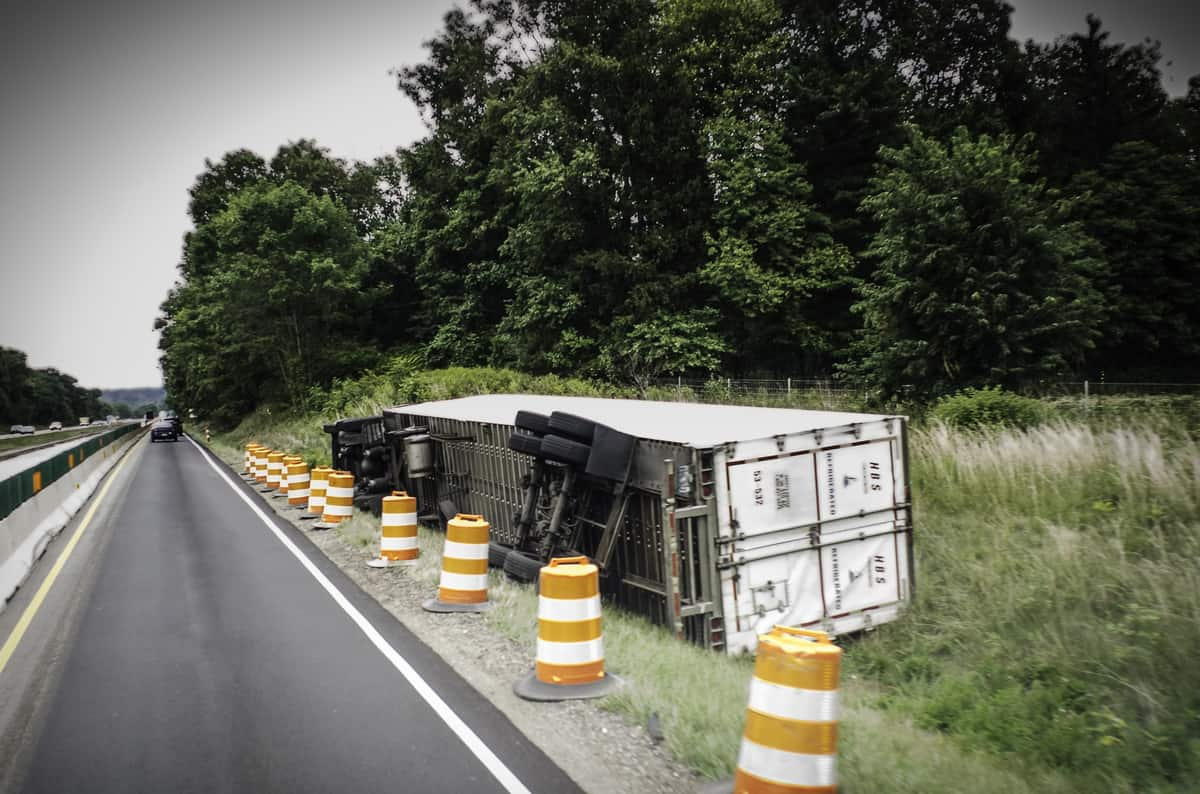 Tractor-trailer flipped on side of a highway.