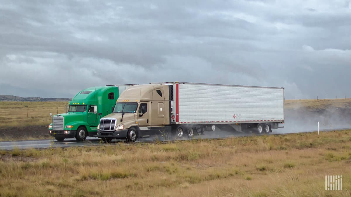 Two tractor-trailers heading down a wet highway.