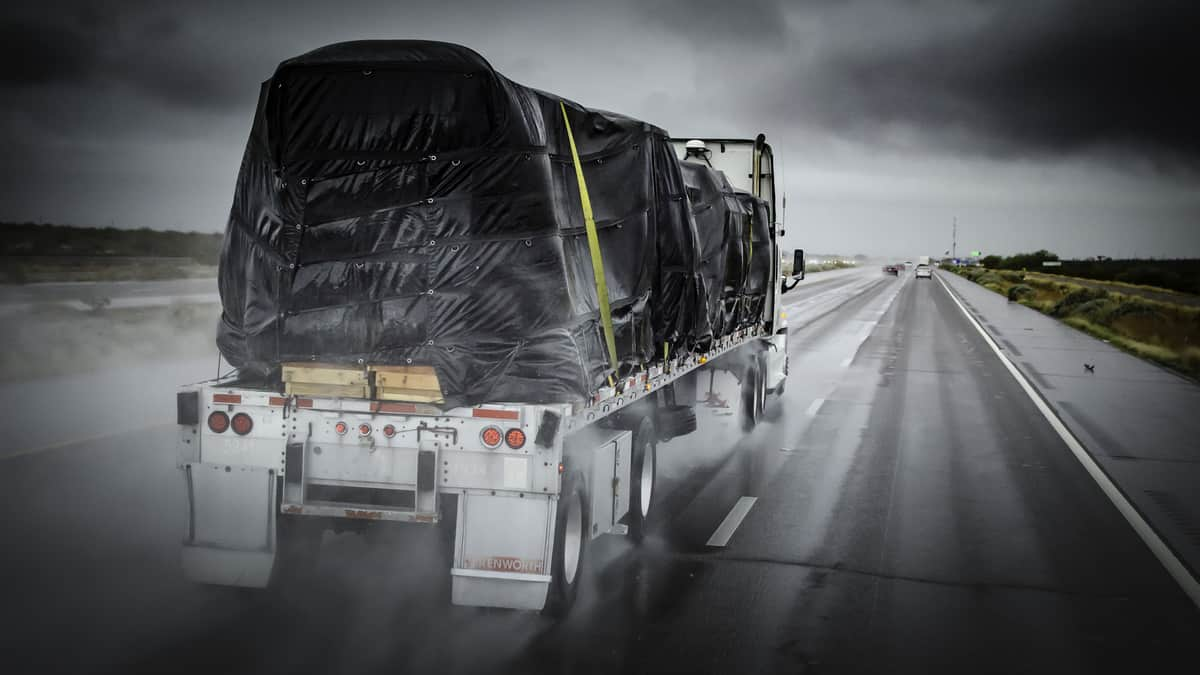 Flatbed, with tarped freight, heading down highway in the rain.
