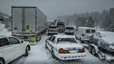 Cars and tractor-trailers stuck in a traffic jam on a snowy highway.
