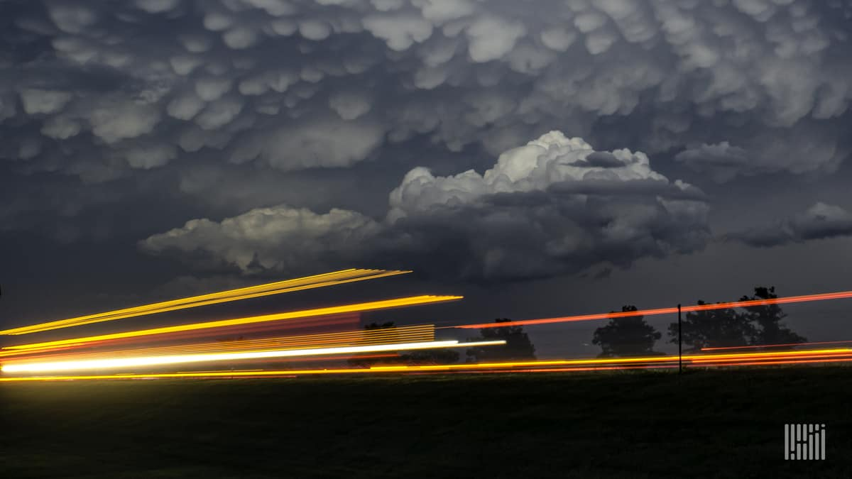 Cars and trucks on a highway, with storm cloud across the sky.