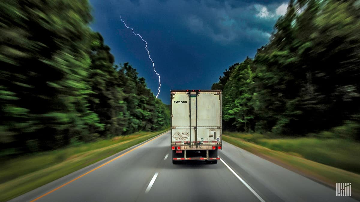 Tractor-trailer heading down a highway with lightning across the sky.