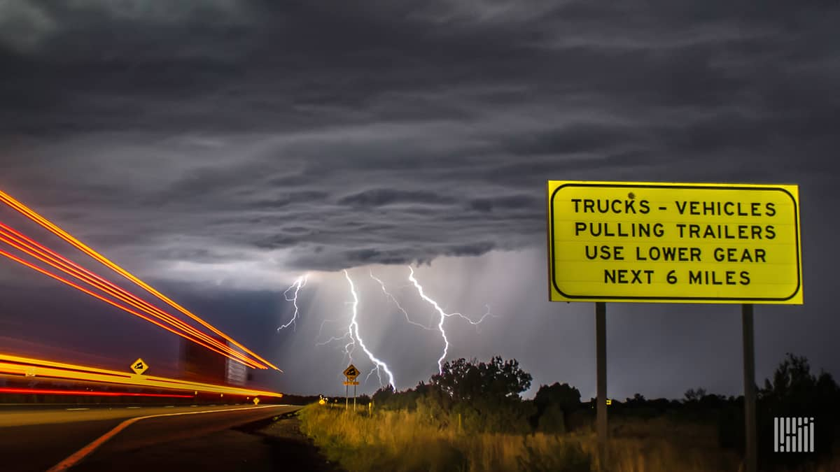 Car and trucks on a highway with lightning bolt coming down from a storm ahead.