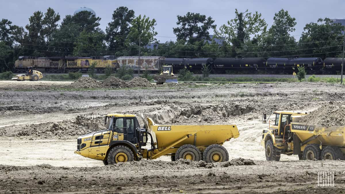 A photograph of a freight train passing through a field while a construction vehicle is in the field.