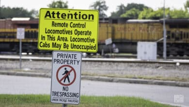 A photograph of a train in a yard. In front of it is a sign that says, Attention. Remote control locomotives operate in this area. Locomotive cabs may be unoccupied.