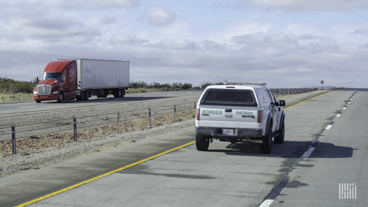 A truck and a border patrol vehicle pass near the U.S. Mexico Border. Cabotage regulations heavily restrict what trucks from Mexico and the Canada can do in the U.S.