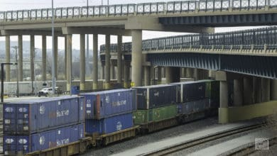 A photograph of a train with intermodal containers traveling underneath a bridge.