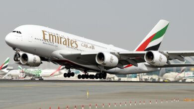 A big, big Emirates A380 jumbo jet lifts off with front wheels off the runway.