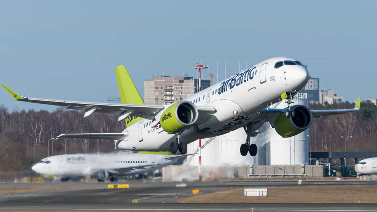 An airBaltic plane with yellow tail takes off on a clear day.