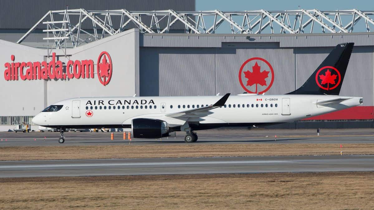 A white Air Canada jet with blue tail taxis in front of large aircraft hangar.