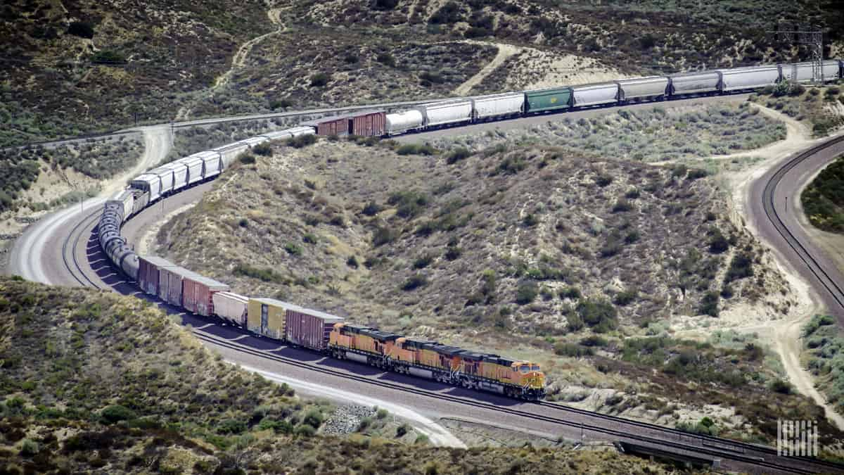 A photograph of a Union Pacific train weaving through a valley.