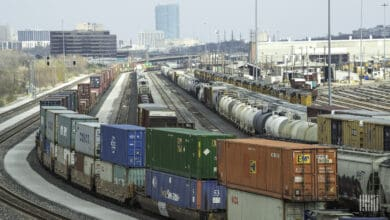 A photograph of a rail yard with a city skyline in the distance.