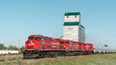 A photograph of a Canadian Pacific train in front of a grain elevator.
