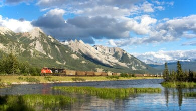 A photograph of a CN train passing by a mountainside lake.