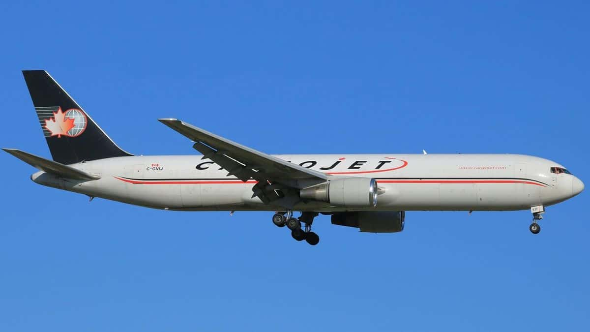 A white Cargojet plane with blue tail in blue sky comes in for landing, with side view from below
