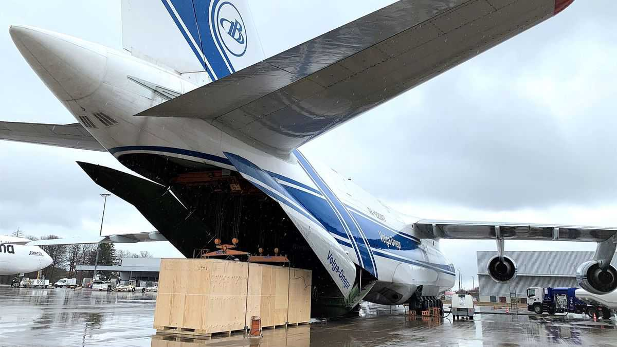The open rear tail of a giant Russian cargo plane unloading a big crate.