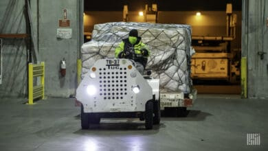 A tractor pulls a cargo pallet.