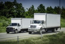 Two expedited delivery trucks on highway