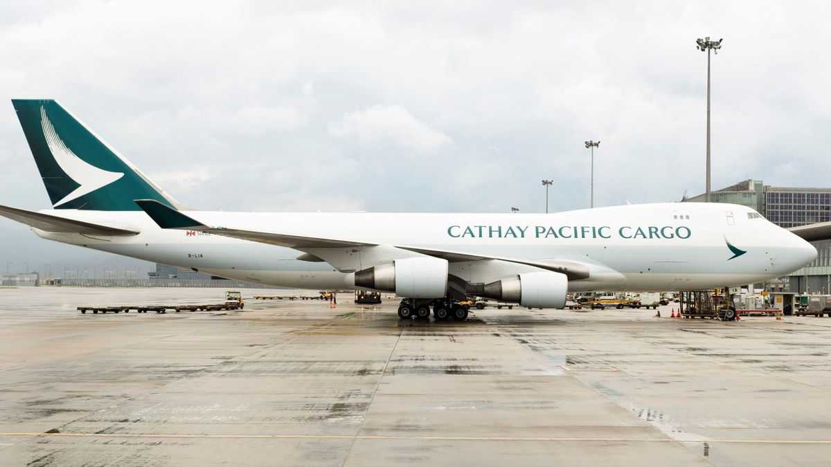 A white 747 jumbo jet with a green tail operated by Cathay Pacific Cargo sits on a wet tarmac.