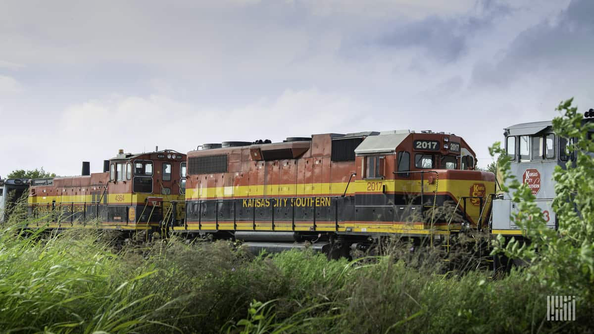 A photograph of Kansas City Southern train traveling through a grassy field.