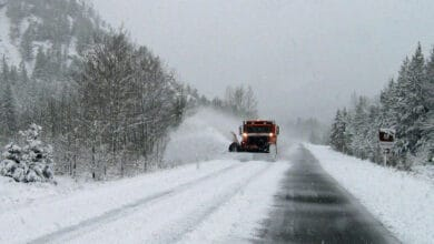 Plow truck clearing snowy Montana highway.