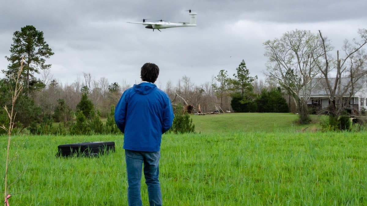 NOAA scientist launching a research drone to take aerial footage of tornado damage.