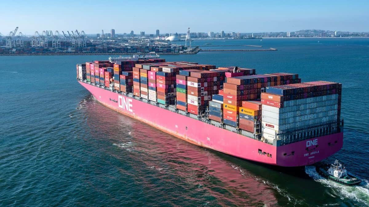 A large magenta colored ship with containers sails into port on a sunny day.