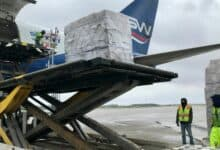 A hydraulic lift helps unload freight pallets from a cargo jet.