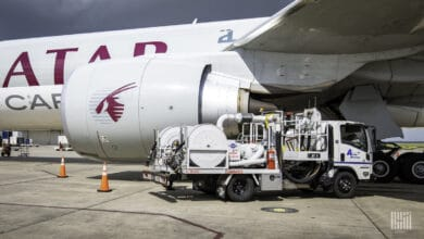 A gray Qatar Airways jet being refueled by a truck.