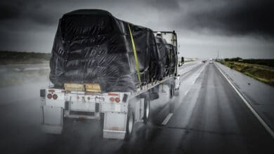 Flatbed heading through the rain with tarp-covered load.