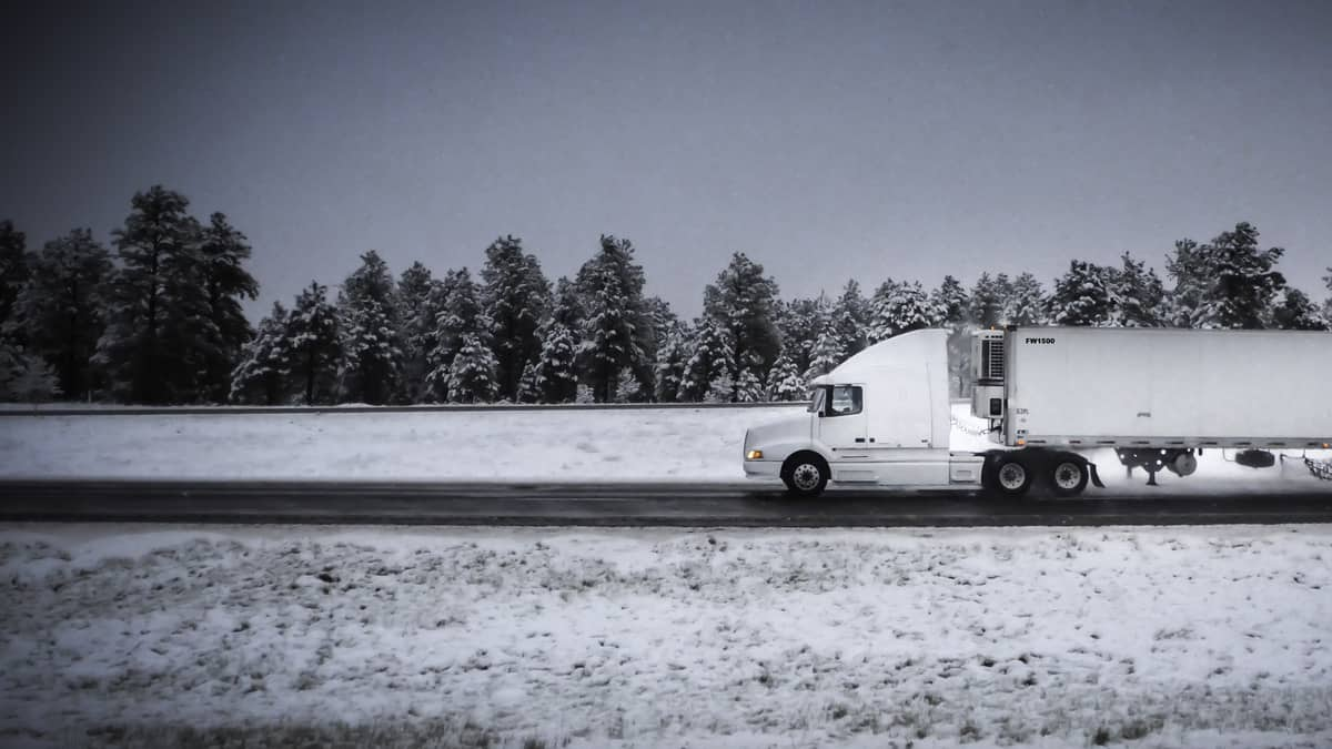 Tractor-trailer heading down highway with some snow on the road and surrounding hillsides.