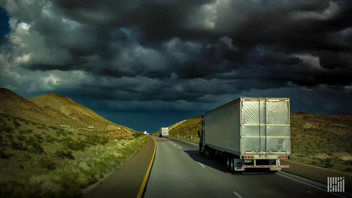 Tractor-trailers heading down a highway with dark storm cloud across the sky.