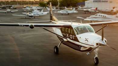 A propeller plane sits in the parking lot of a general aviation airport.