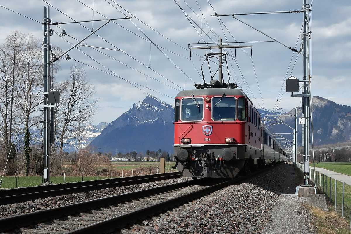 A photograph of a train on a track. The train is connected to catenaries.