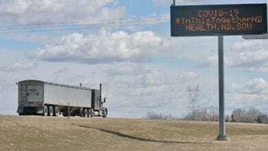 A truck passes a sign reading: COVID-19: In this together. To illustrate a story about North Dakota vaccinating Canadian truck drivers.