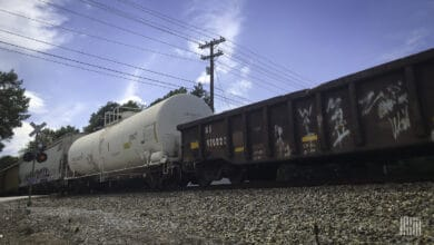 A photograph of rail cars rolling by a railroad crossing.